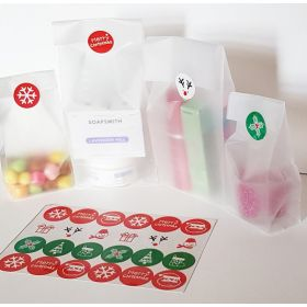 "Pack of 20 Small clear frosted block bottom sweet/party/gift bags (3"" x 2"" x 7"") with assorted printed Xmas symbols sticky labels"